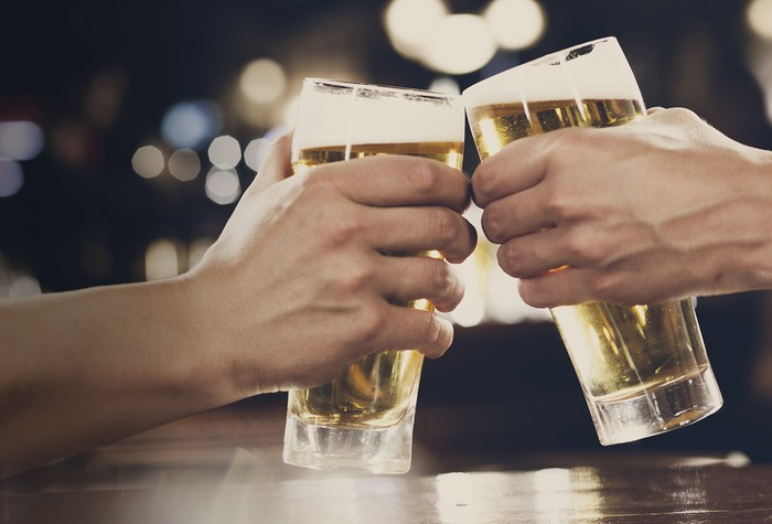 Two hands clink beer glasses together in a toast.