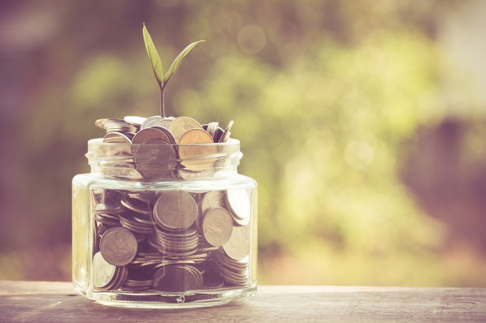 Jar of coins with a sprout growing out of it.