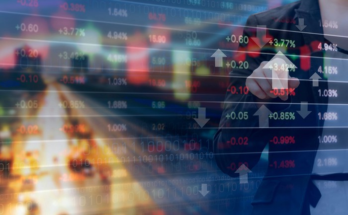 Double exposure of businesswoman and stock market graph with city in the background.
