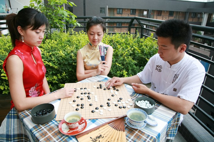 Three people sitting at a table while two play the Chinese game of Go.