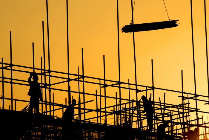 Silhouette of construction workers working on a building.