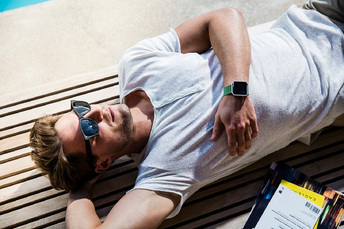 Man in t-shirt and sunglasses lying down relaxing with Fitbit on his wrist.