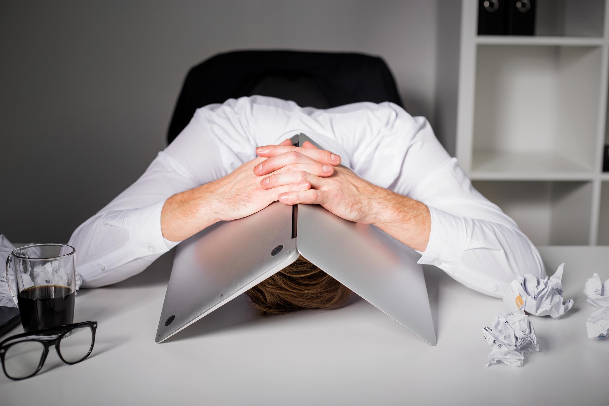 An upset man hides under his laptop.