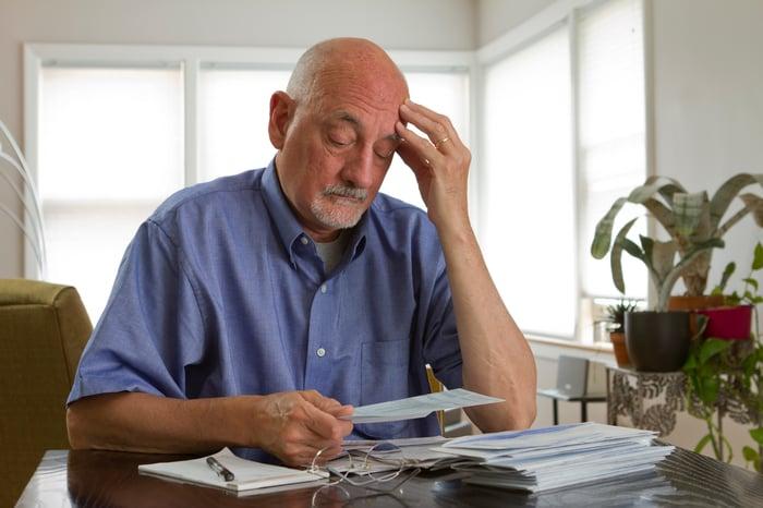 Senior man looking worried, staring at a stack of paperwork.