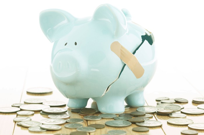 A blue piggy bank has a bandage over a large crack on its side, with coins spilled out beneath it.