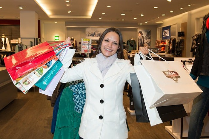 A woman shopper holding a number of shopping bags.