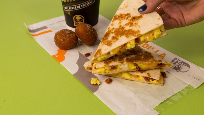 A hand picks up a Taco Bell breakfast quesadilla.
