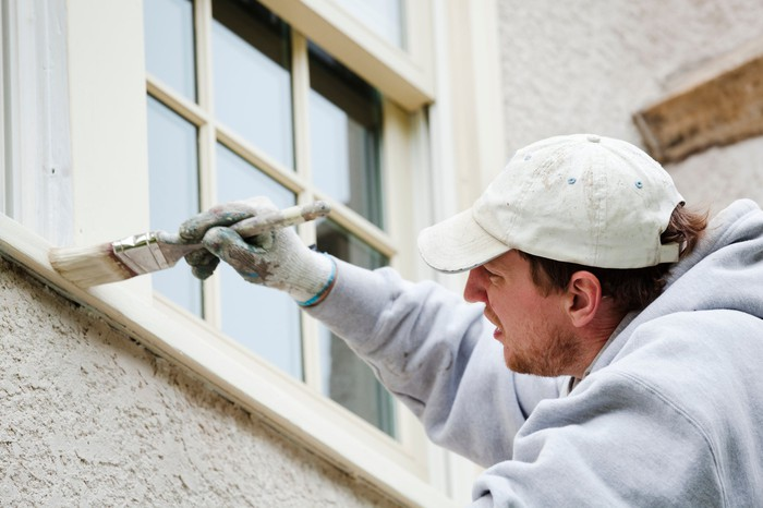A man applies paint to trim beneath a window.