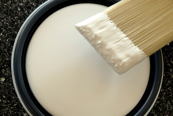 An overhead view of a paint brush and gallon of white paint.