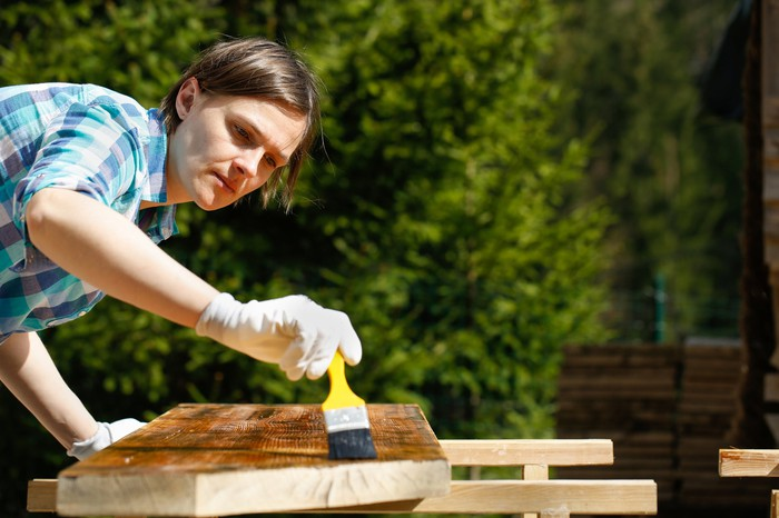 A woman uses a brush to apply stain to a board.