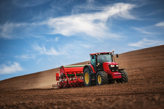 A red tractor tilling a field.