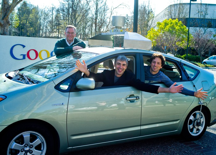 The three men are leaning out the windows of a modified Prius, parked in a Google parking lot.