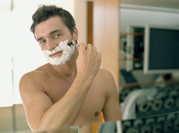 A man shaving in a mirror.