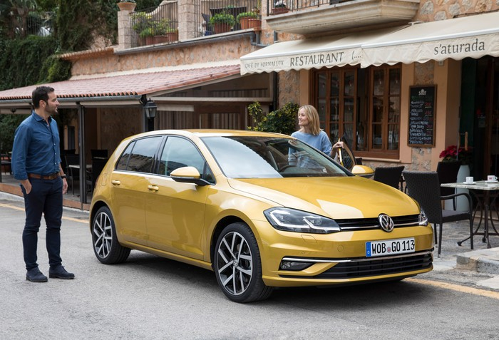 A yellow VW Golf in front of a restaurant.