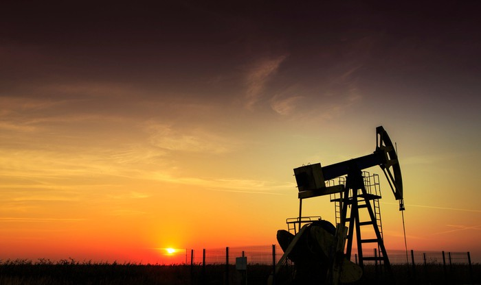 Drilling rig with setting sun in the background.