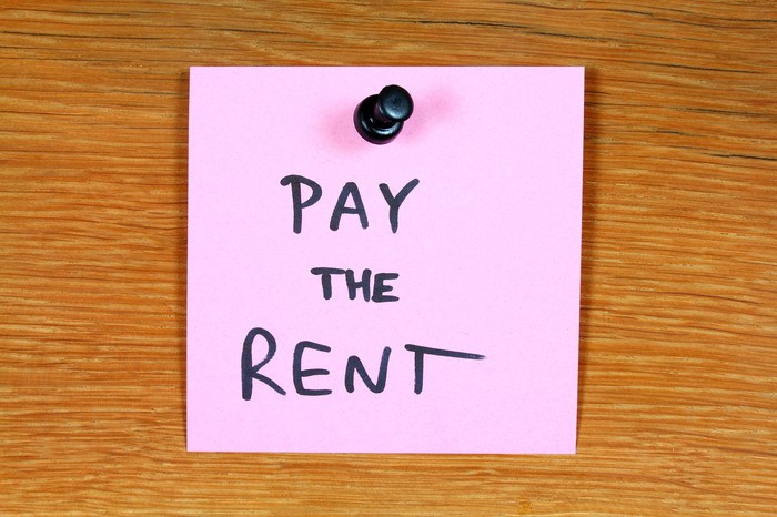 "A pink sticky note reading ""pay the rent"" is tacked to a wooden surface."