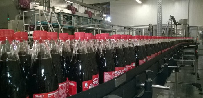 Coke bottles coming down the line in a bottling plant.