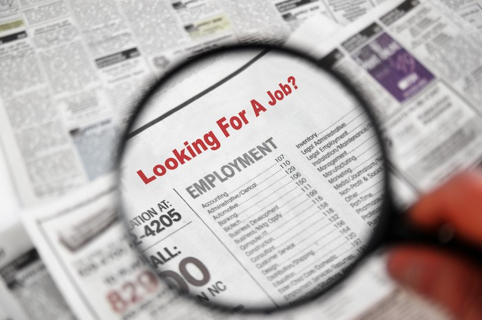 Browing the employment classifieds in a newspaper.