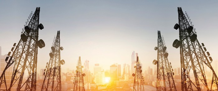 A series of telecom towers are silhouetted in the foreground in front of a city scape as the sun rises.