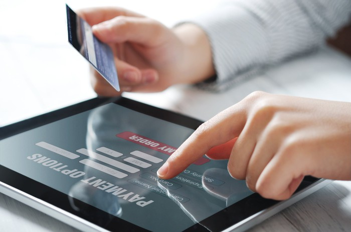 A person holds a credit card while shopping on a tablet.