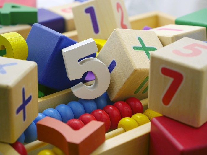 Blocks, numbers, and an abacus lie in a pile.