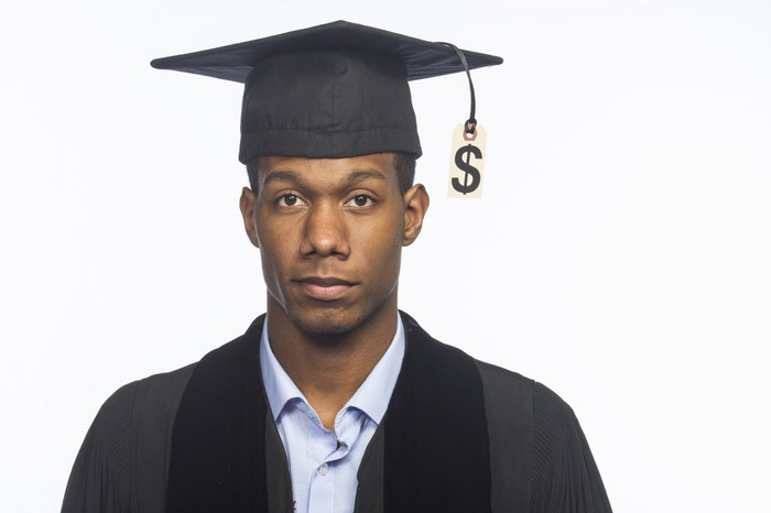 Young man wearing mortarboard with price tag hanging from tassle