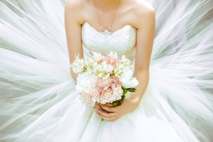 Bride wearing white wedding dress and holding bouquet of flowers.