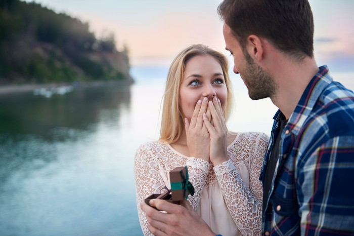 Young man proposing to surprised-looking girlfriend with ring in his hand
