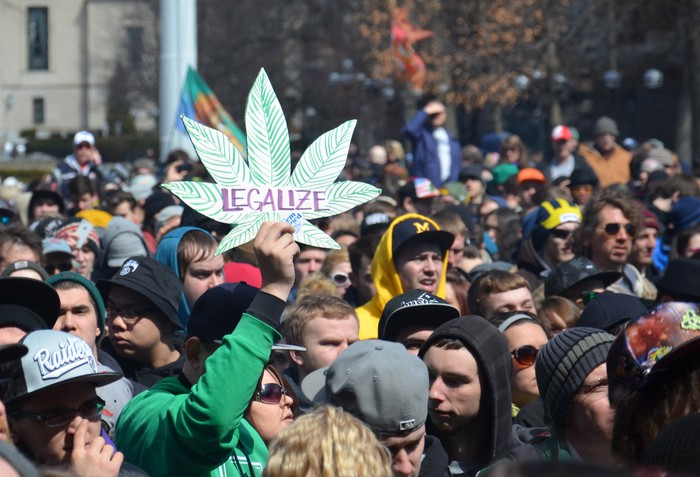 "A person holds up a sign that reads ""legalize"" at a pro-marijuana rally."