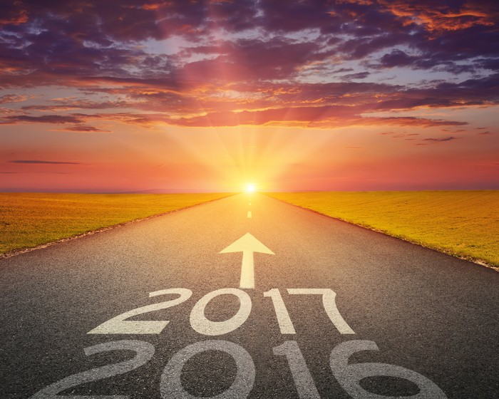 "The numbers ""2016"" and ""2017"" with an up arrow above them on an empty road leading to a shining sun"
