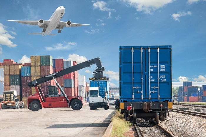 Freight being loaded onto trucks while an airplane flies overhead.