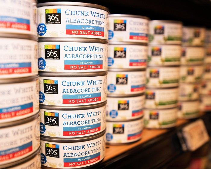 Cans of Whole Foods 365 tuna, stacked on a store shelf.