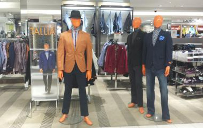 The inside of a Macy's store with men's attire on display.