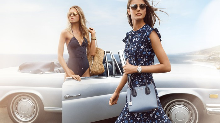 Two models sporting Michael Kors handbags.