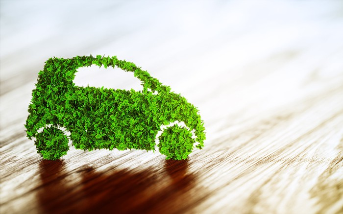 """A cutout """"green"""" car made of leaves or tissue paper, on a wooden surface"""