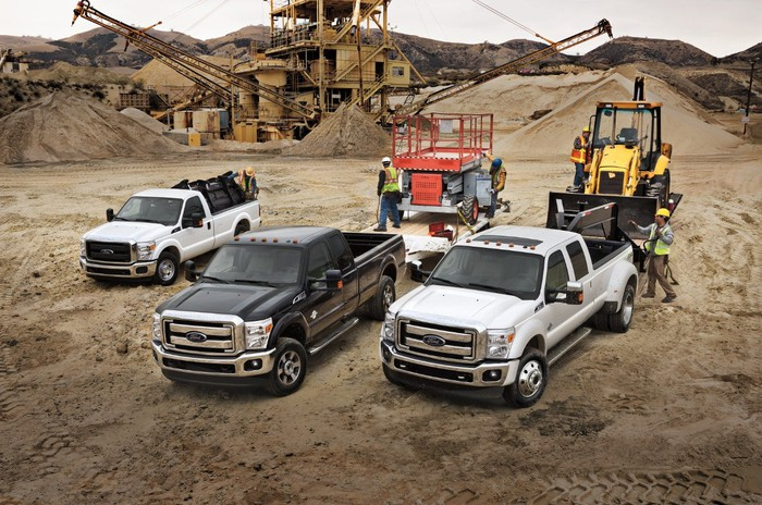 Three F-Series Super Duty trucks at a work site.