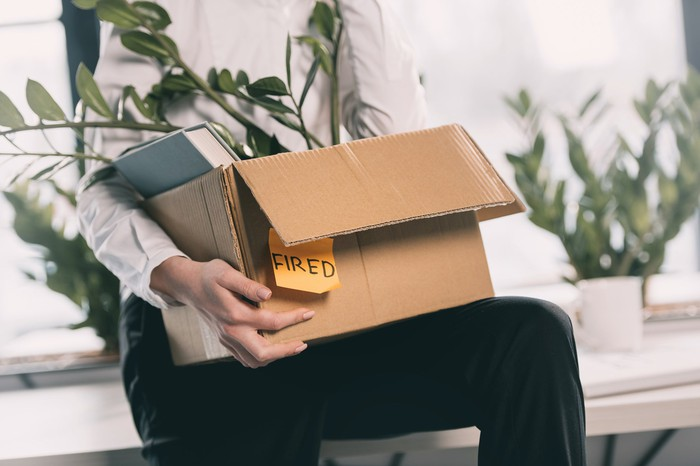 "Employee carrying box with ""Fired"" Post-It Note"