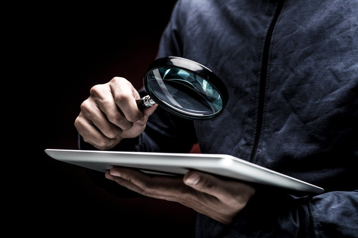 A man looks at a tablet with a magnifying glass.