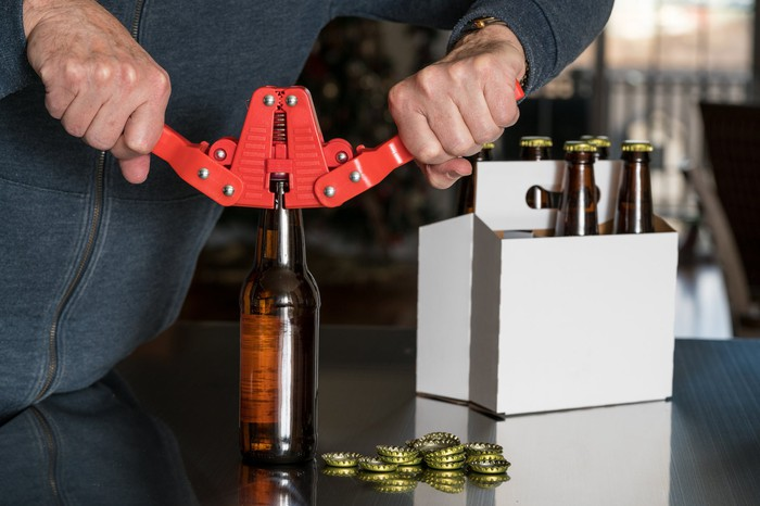 A home brewer caps beer bottles