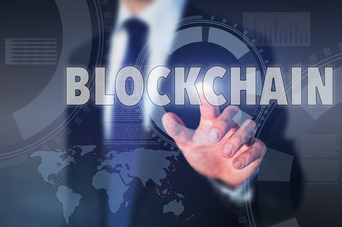 """A man's finger touches the word """"blockchain"""" on a transparent screen."""