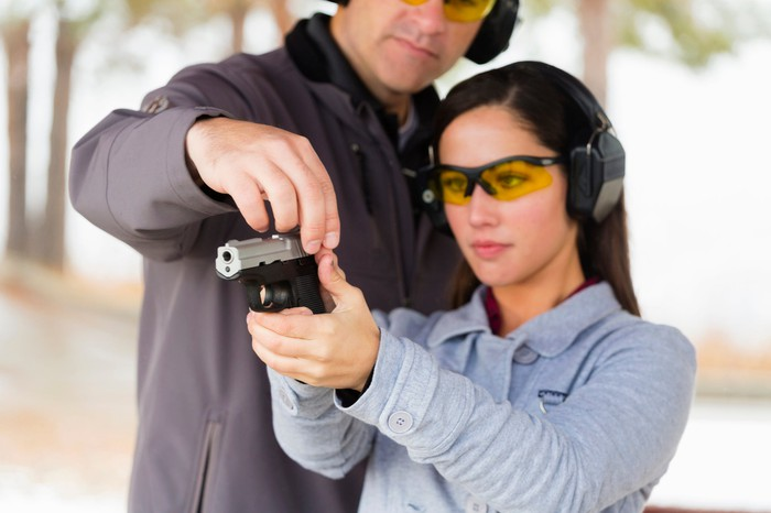 A woman receives instruction at a gun range.