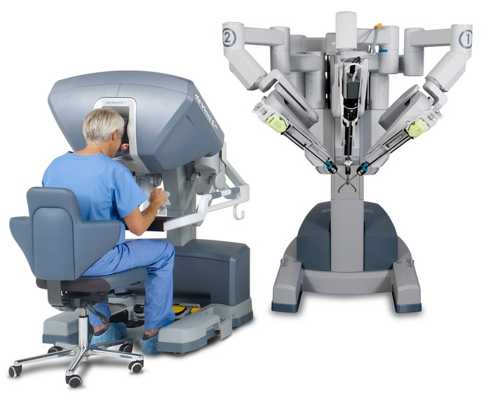 A man sits at the controls of an Intuitive Surgical da Vinci system.