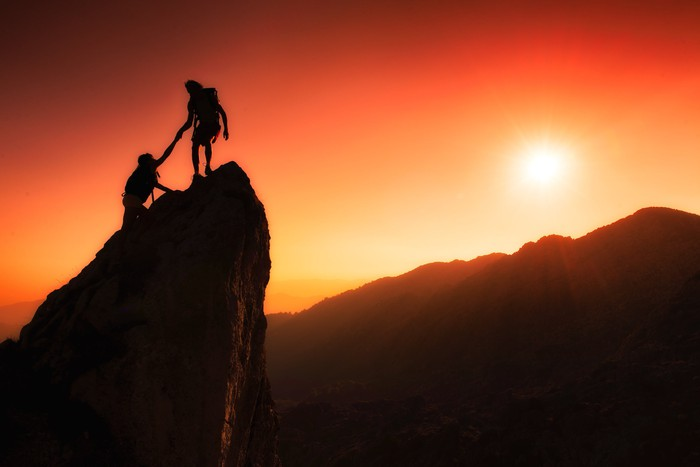 Two mountain climbers reaching the summit at sunset.