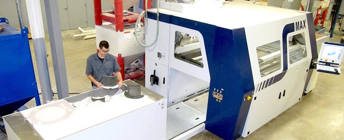 A man working next to ExOne's large S-Max 3D printer.