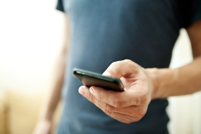 A man touches the screen of a smartphone cradled in his hand.