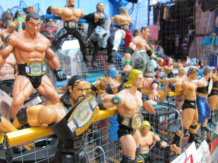 Wrestling figures are posed on a store shelf.