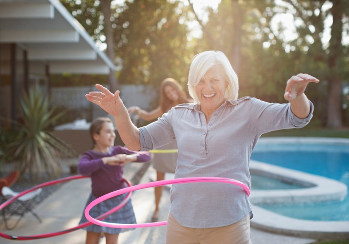 A senior women uses a hula hoop near a swimming pool with her grandkids.