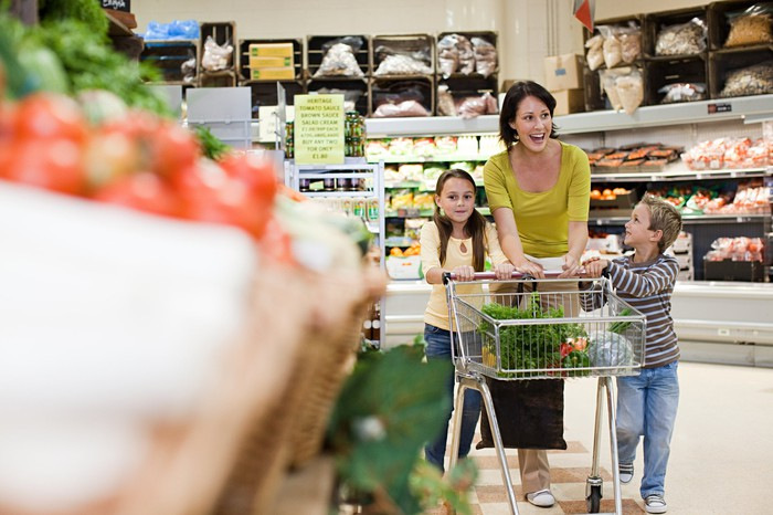 A woman pushes a shopping cart through a grocery store, accompanied by two children.