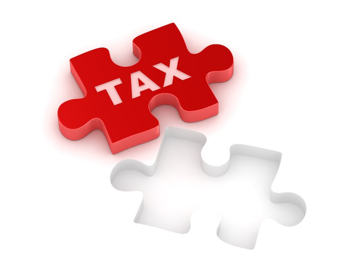 "Red jigsaw piece on which is written ""tax,"" fitting into its space"