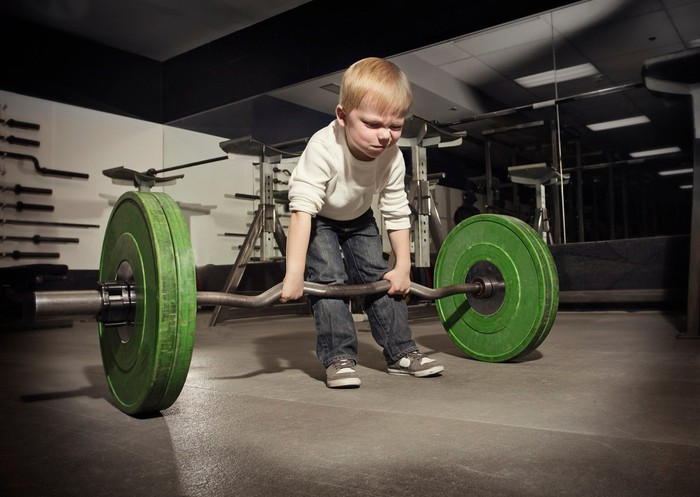 A small child tries to lift a very heavy barbell.